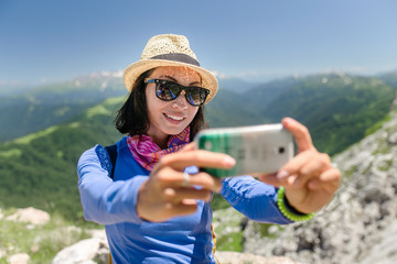 woman traveler in the mountains makes selfie on smartphone