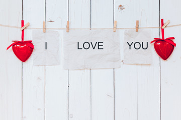 Red heart and old paper with text I LOVE YOU hanging at clothesl
