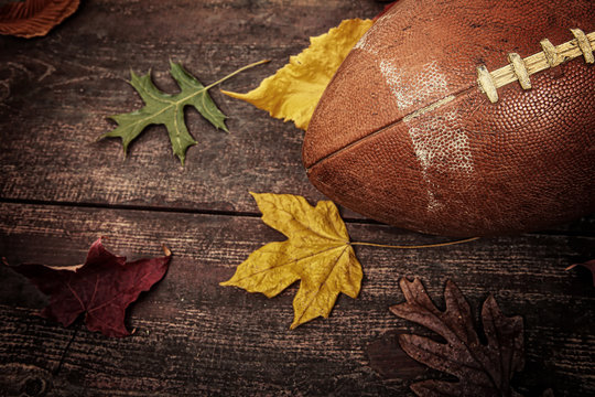 Old worn football with autumn leaves