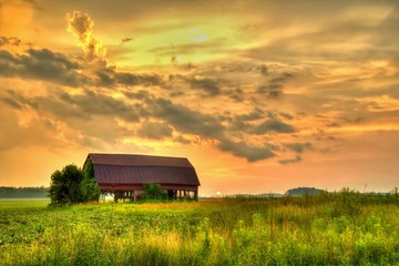 Wooden Barn Sunset. Rural sunset with an abandoned barn surrounded by farm fields. Wall mural