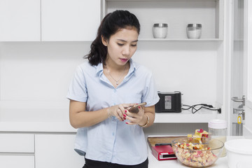 Housewife looking smartphone in kitchen