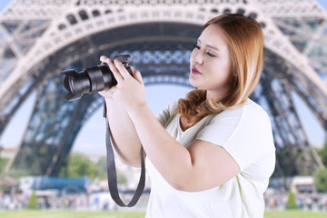 Woman taking picture at eiffel tower
