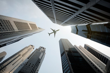 An airplane flying above skyscrapers seen from below.