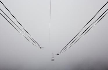 A cable car moving through fog.
