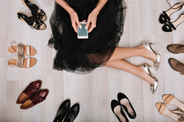 Stylish girl sitting on the floor in a dressing room with smartphone in hands, writes  the message, surrounded by a variety of shoes. She is dressed in a black skirt, on her feet silver luxury shoes