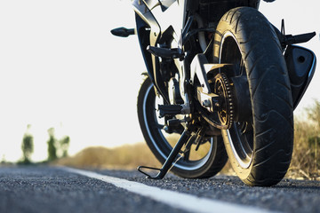 A motorcycle parking on the road right side and sunset, select focusing background. Wall mural