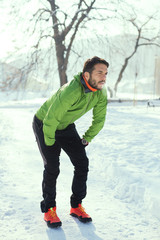 Handsome young runner on the snow.Colored photo