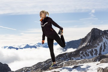 A young woman stretching in the Alps.