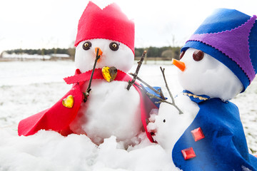 Two cute snowmen dressed as kings with crowns and capes looking very regal. Snow fall background in a rural winter scene