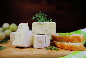 сыр камамбер с зеленью,виноградом и багетом на сервировочной доске