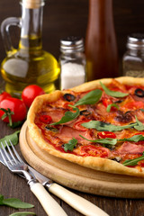 Mediterranean traditional pizza with ham, tomatoes, olives and herbs on wooden table.