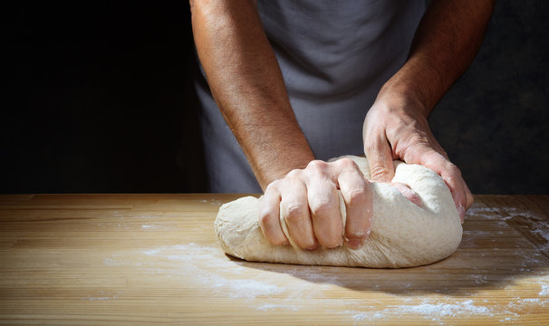 Baker's hands make the dough for bread or pizza on a wooden pastry board. Closeup, space for text.