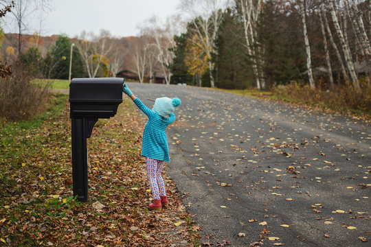 Girl collecting letter from the mail box in the street