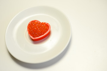 Red caviar in a heart shape on white plate background