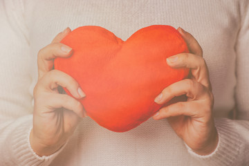 Female hands holding red toy heart. Valentines day concept. Retro toned picture.