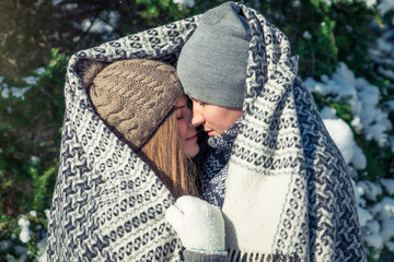 Couple in love covered with blanket hugs in winter forest