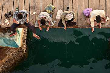 Group of people fishing from a wooden pier, Bima, Indonesia.