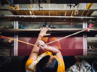 A woman working on a loom, Maheshwar, India.