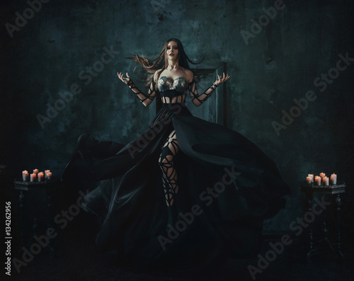 Beautiful witch floating in the air. Background dark room. Girl dressed in a black dress with a long train.