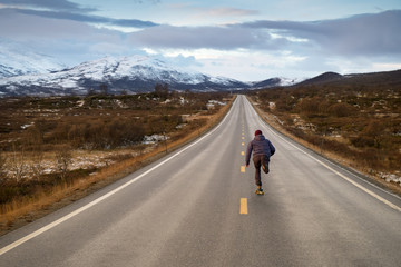 A man running down a road with mountains in the background.