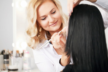 Make up artist applying face powder to a customer in a beauty store
