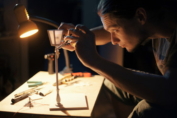 A man making a tiny street lamp.