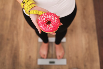 Young beautiful woman standing on scales and holding a donut. The concept of healthy eating. Healthy Lifestyle. Diet.