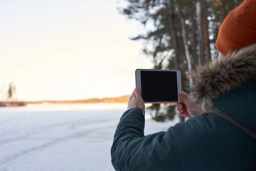 Man in hipster clothes keep tablet outdoor in winter time. Guy make snapshot of snow contryside. Talking with help of internet technology in the forest. Travel concept with free space of advertising.