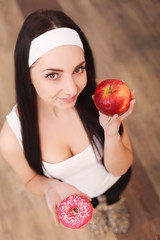 Beautiful young woman making choice between apple and donut on wood background