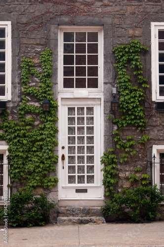 White Front Door And Sash Windows. Green Vines Climbing Up Stone Wall.  Stone Front