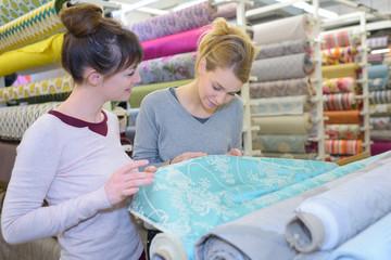 Women examining roll of material