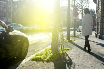 Rear view of elegant woman walking on a sunny empty French street