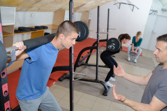 teen training with weights at gym club with coach