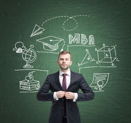 Man in suit and education icons on blackboard