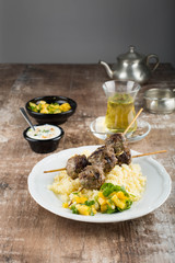 Moroccan meatballs served over couscous. Mint tea in the background. White plate on a rustic wooden tabletop.