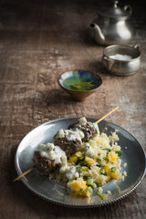 Moroccan meatballs served over couscous on a vintage pewter plate. Mint tea in the background.