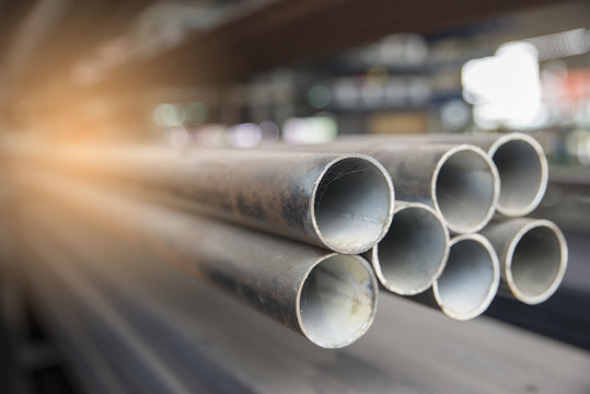 Steel pipes used for construction in warehouse. Metal tube for building at construction site.