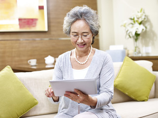 senior asian woman using tablet computer