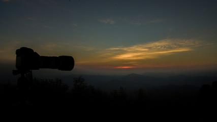 Camera on the tripod shooting on the peak of mountain