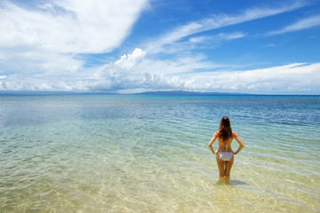 Young woman in bikini standing in clear water on Taveuni Island,