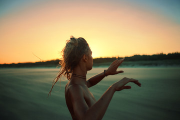 Woman dancing in the sunset on the beach