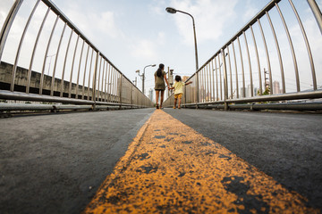 Wide angle view of straight yellow line on bitume floor, footbridge, walkway and stairs, perspective with vanishing point, city urban background