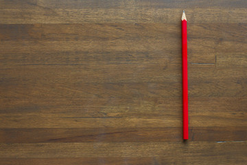 red pencil on wooden background
