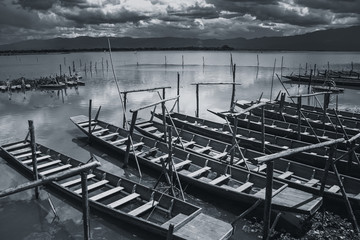 empty wooden fishing boat parking at lake shore  in quiet lake sky black and white tone.