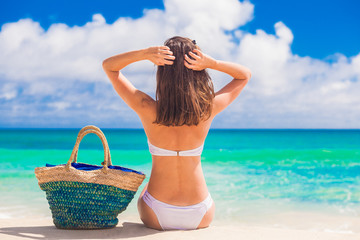 woman in white bikini with straw bag relaxing at beach. Mahe island, seychelles