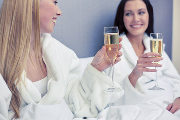 happy women in bathrobes with champagne glasses