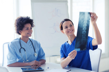 happy female doctors with x-ray image at hospital