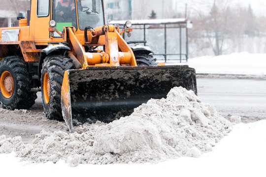excavator clears snow from roads