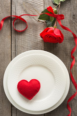 Romantic dinner concept. Festive table setting for Valentines Day on wooden background. Red rose with ribbon and heart on plate.