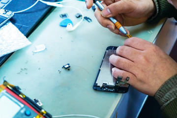 man technician repairing mobile phone